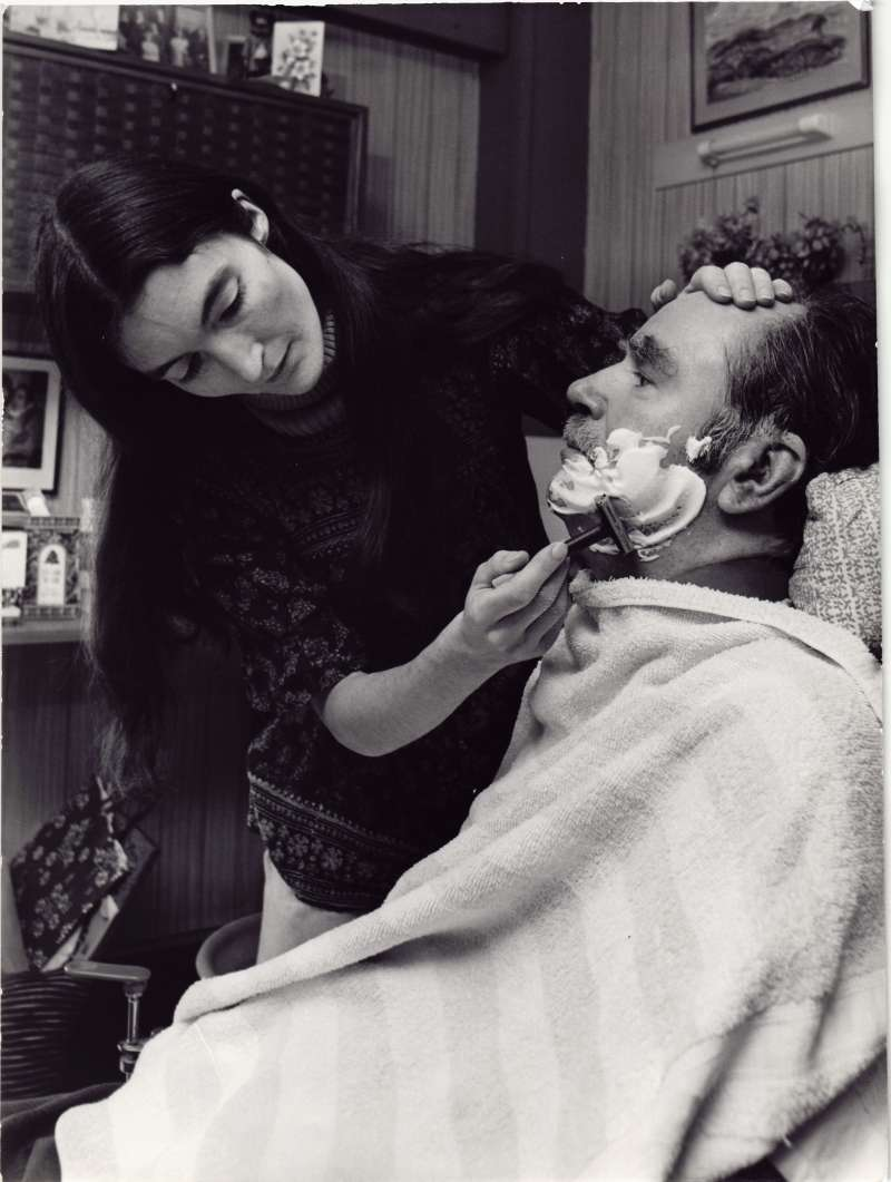 A male resident with shaving foam on his face being given a wet shave by a woman