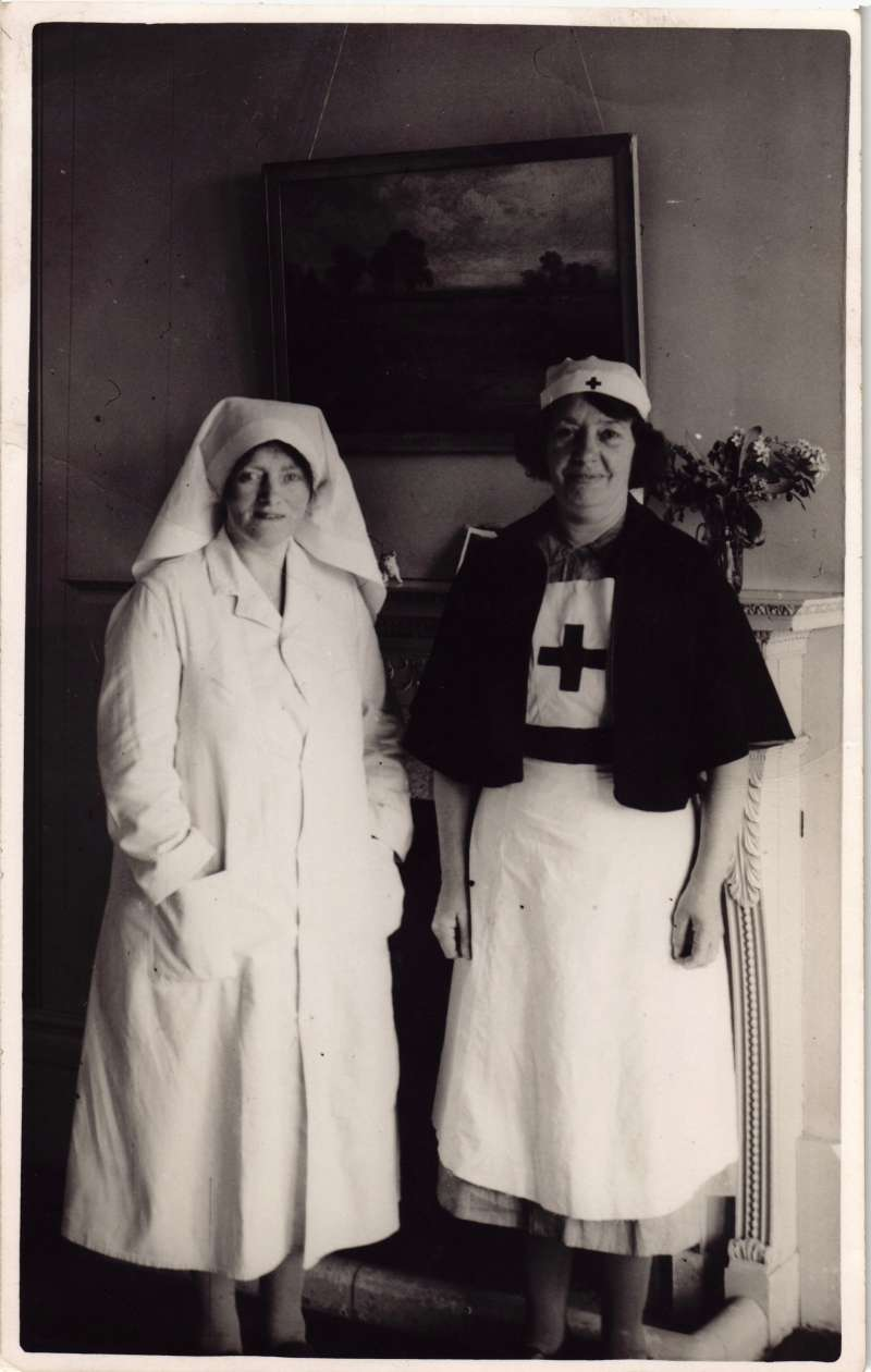 Two nurses in full uniform standing in front of a fire place