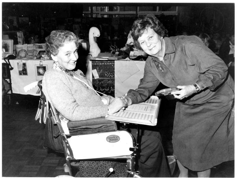 Woman in a wheelchair receiving an award from another lady, with a table of crafts behind