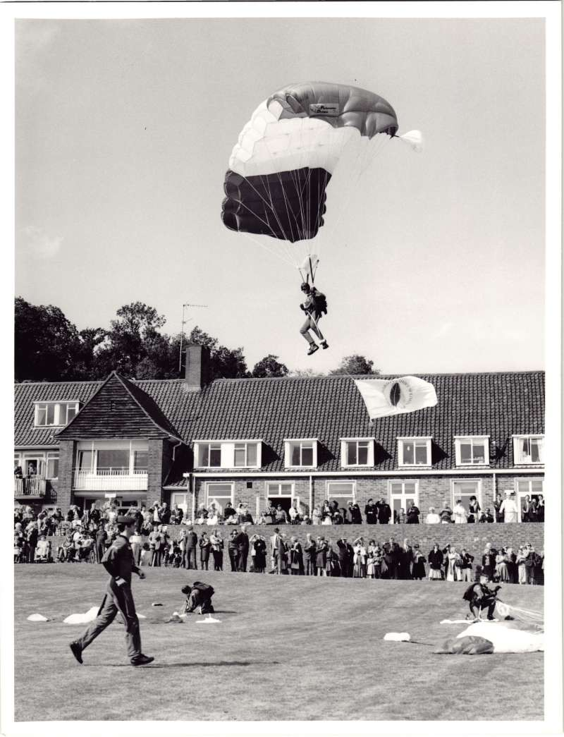 Parachuting soldiers landing on the lawn, with crowds watching in the distance