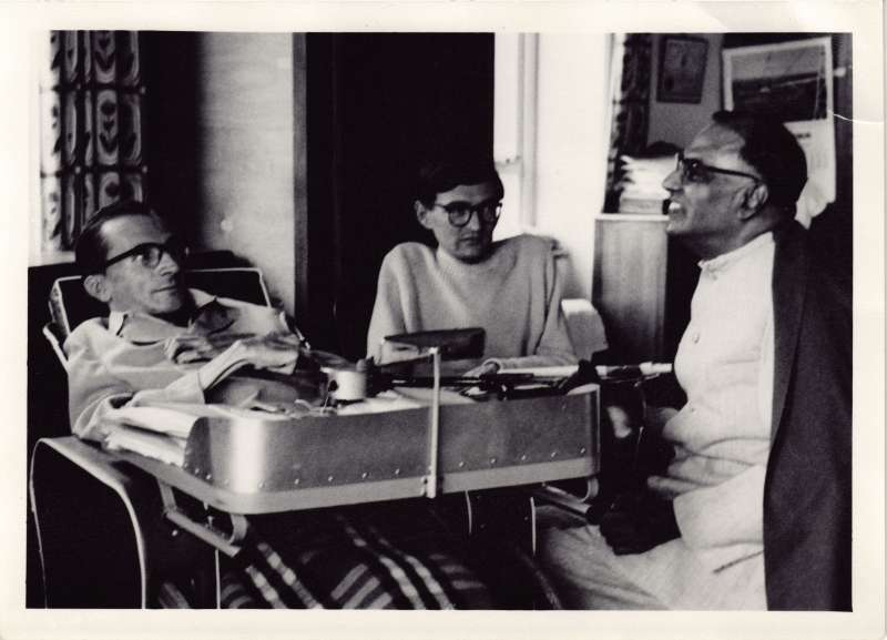 Three men, one in a large wheelchair, talking in a bedroom