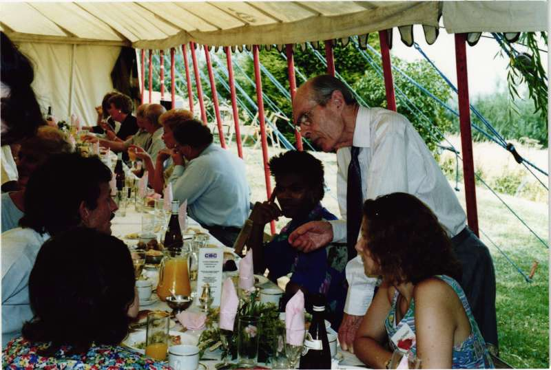 Leonard Cheshire standing talking to male and female residents at a table inside a marquee