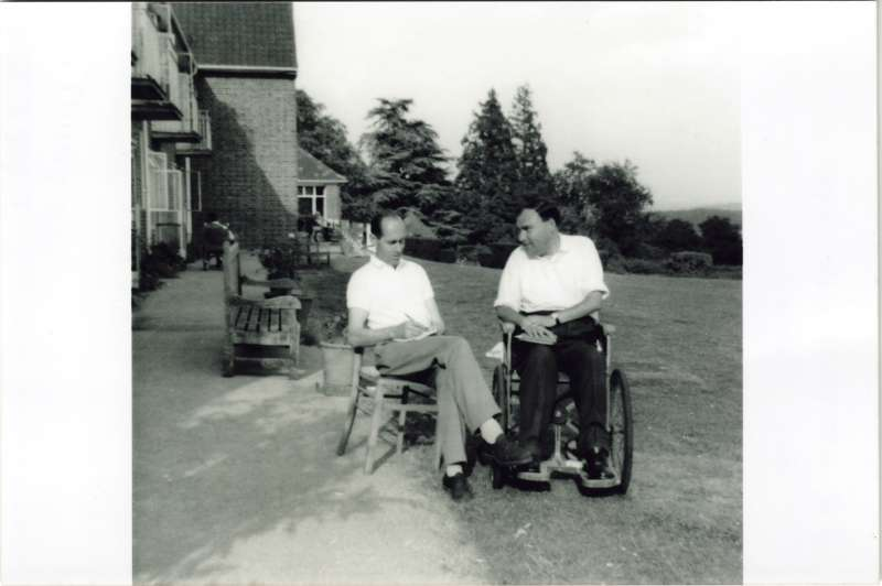 Leonard Cheshire in a chair talking to a man in a wheelchair in the gardens at Le Court
