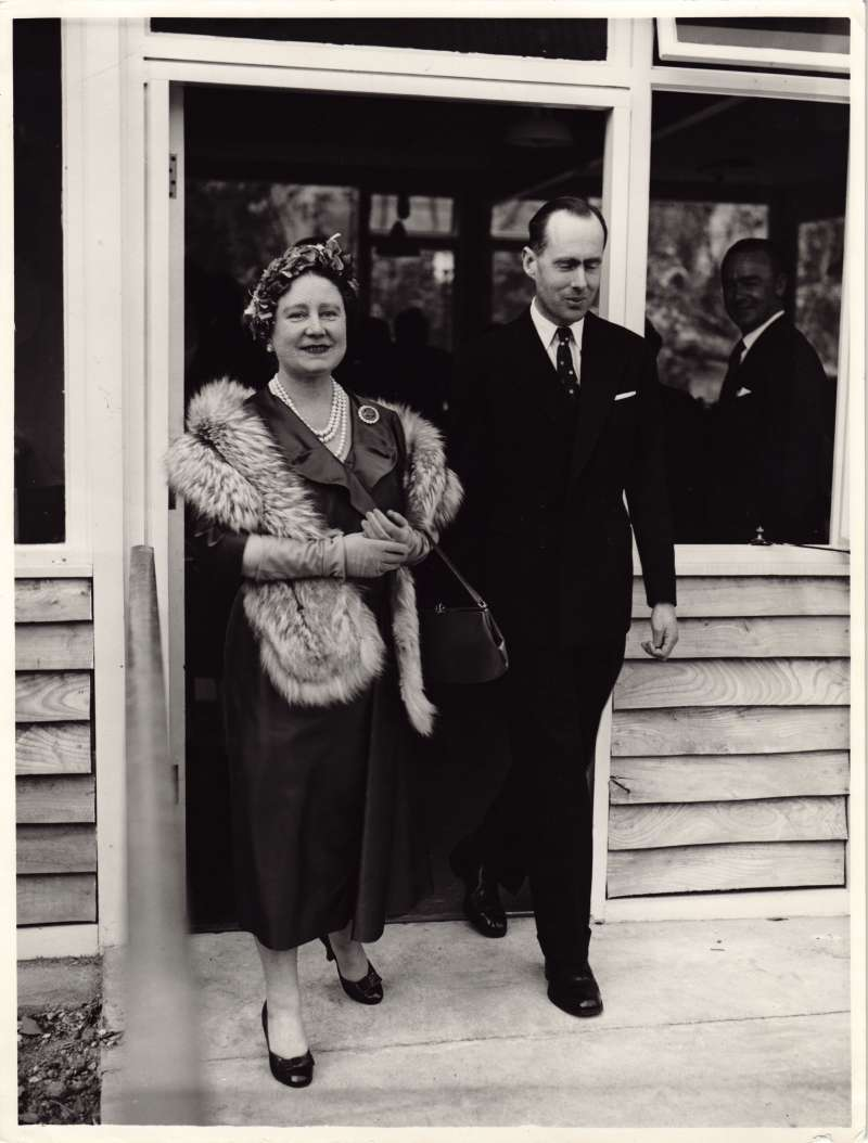 Leonard Cheshire and the Queen Mother walking through a doorway towards the camera