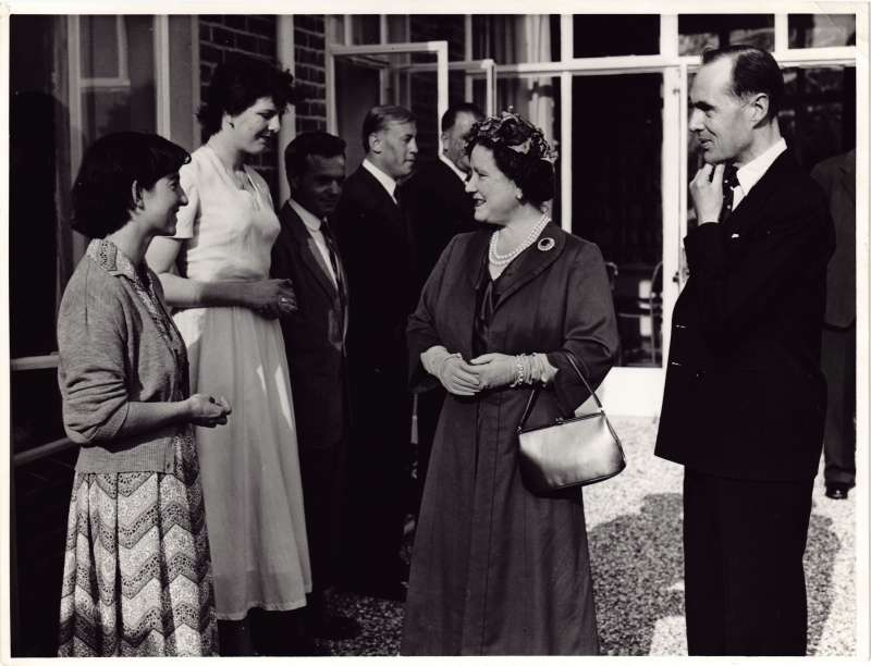 The Queen Mother talking to two female staff members with Leonard Cheshire watching on