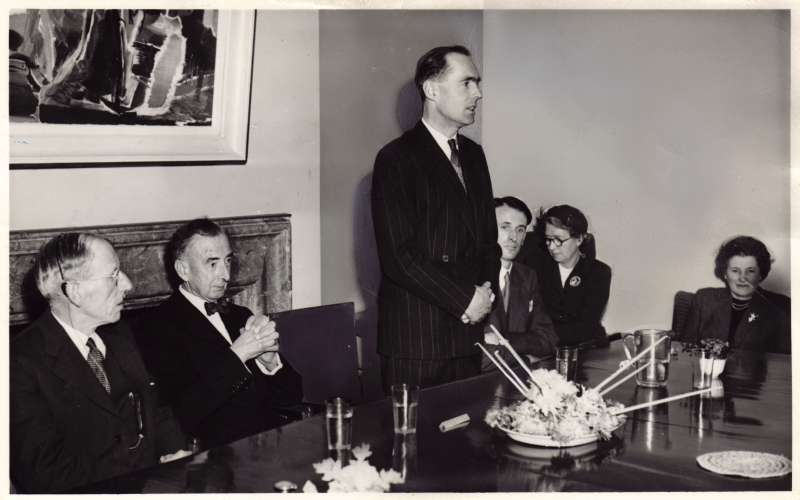 Leonard Cheshire making a speech at a table with others watching on