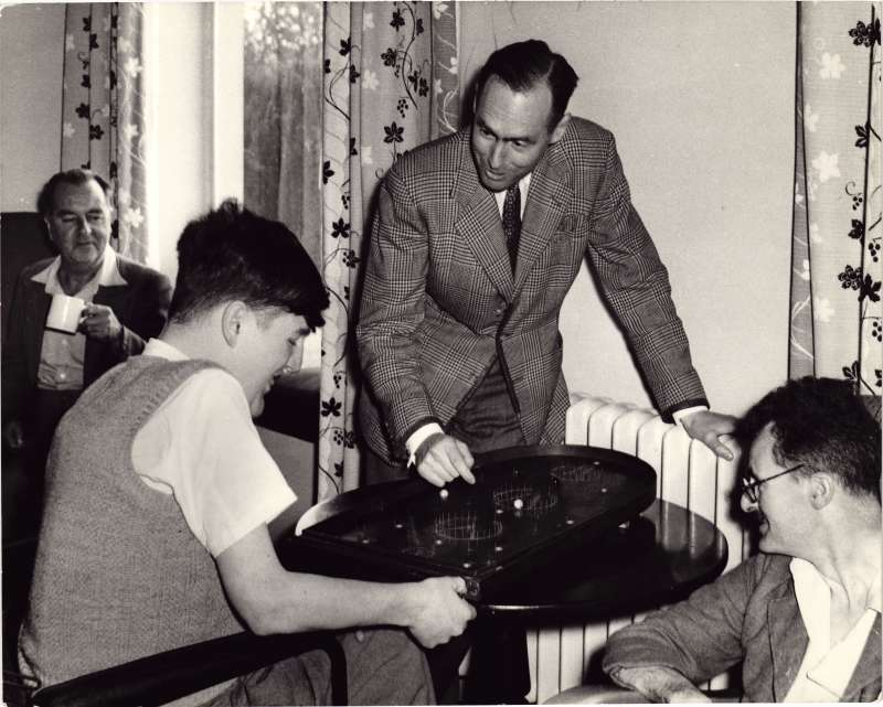 Leonard Cheshire standing, playing a pinball game with two male residents