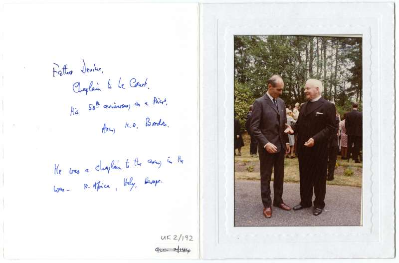 Photo inside a card. Leonard Cheshire talking to a priest in the grounds at Le Court