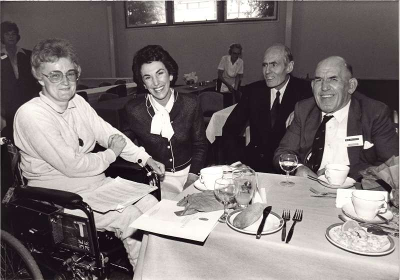Photo showing a woman in a wheelchair with Edwina Currie and Leonard Cheshire and another man at a dining table