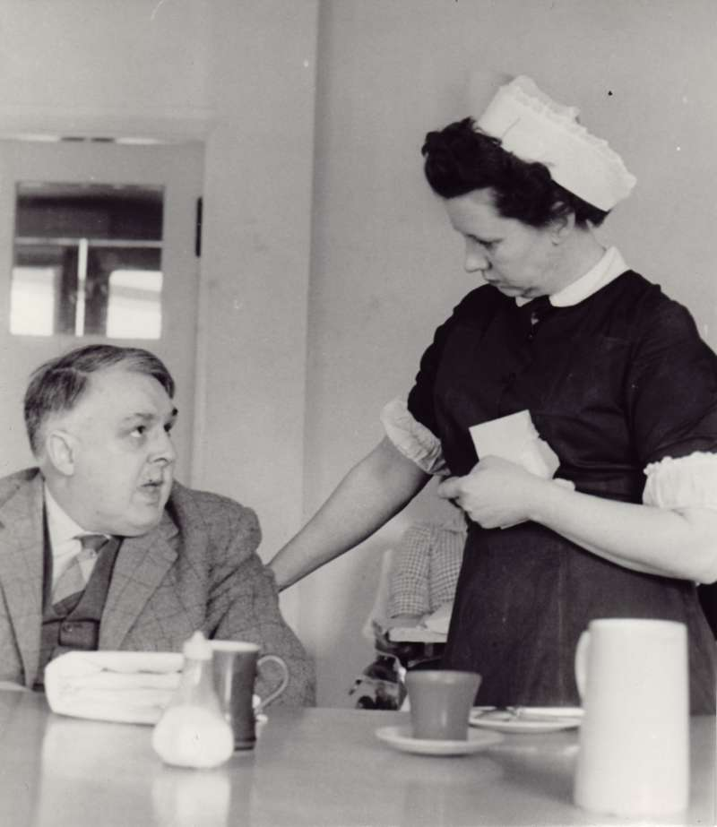 Woman in a nurse's uniform talking to a man sat at a dining table with teacups on