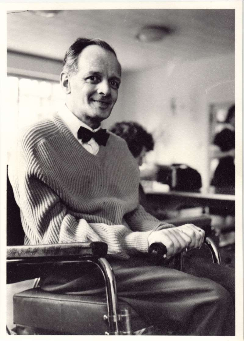 Close up of a man in a wheelchair wearing a bow tie looking at the camera