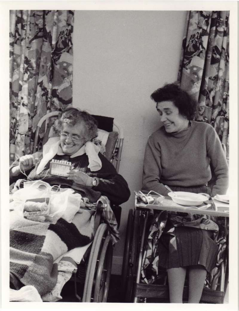 Two women in wheelchairs laughing. One doing needlework, one with a food bowl on a table across her chair