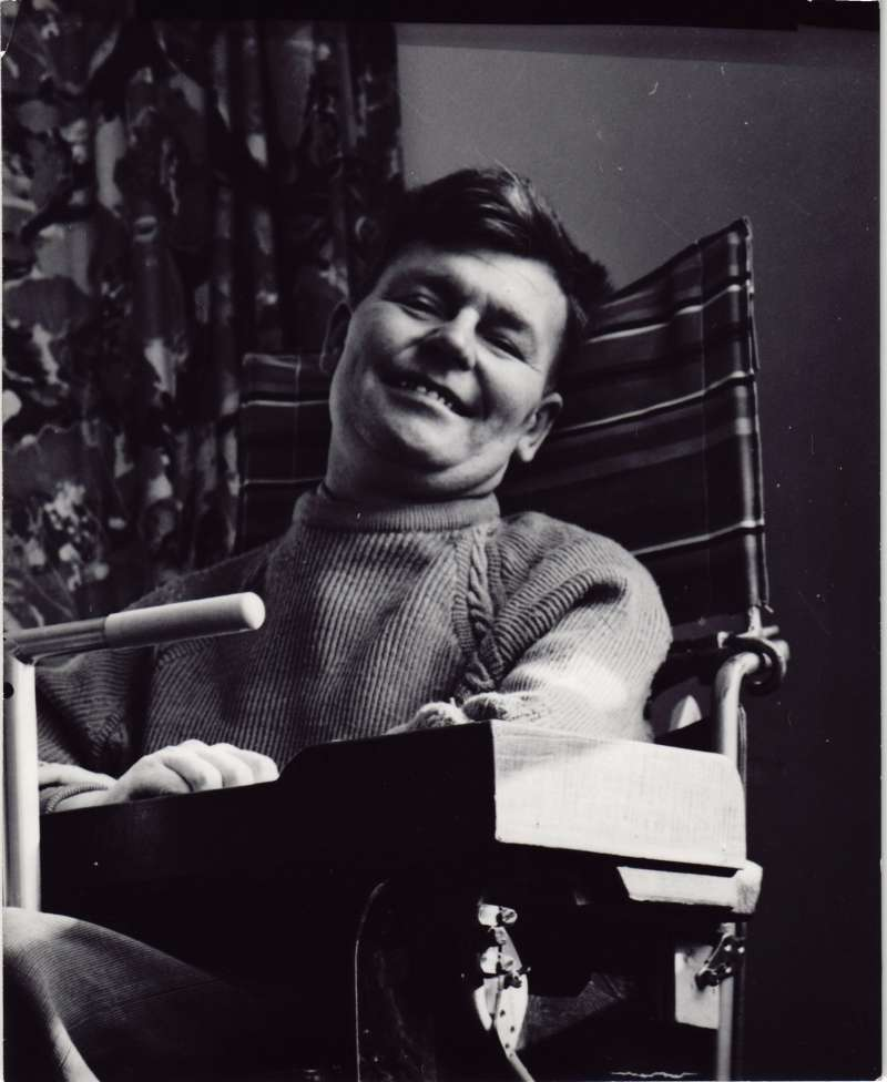Close up of a man in a wheelchair smiling at the camera