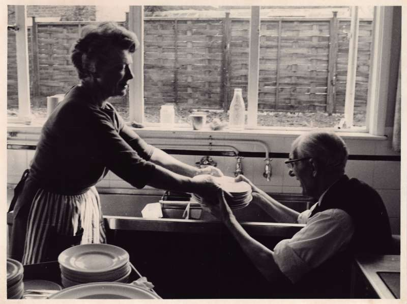 Woman standing, handing a pile of dishes to a man in a wheelchair in front of a kitchen sink