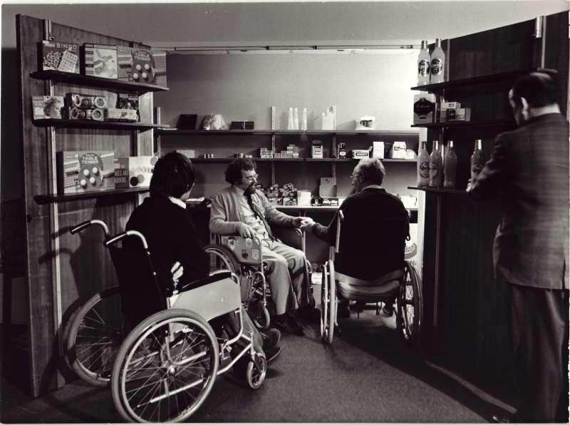Three men in wheelchairs in a room with shelves stocked with shop supplies