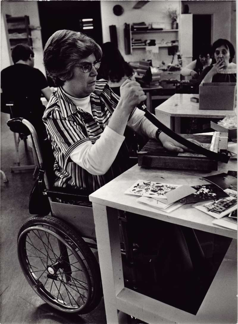 Woman in a wheelchair using a guillotine to make greetings cards in the foreground, with other residents at tables in the background