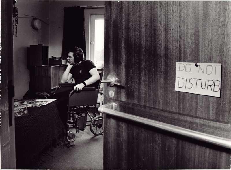 Shot of an open door into a bedroom with a man in a wheelchair wearing headphones. Sign on door says 'Do not disturb'