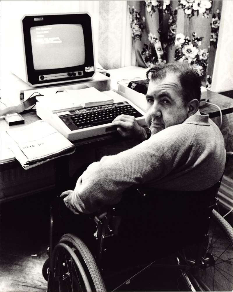 Man in a wheelchair sat a table with a computer, smiling back at the camera