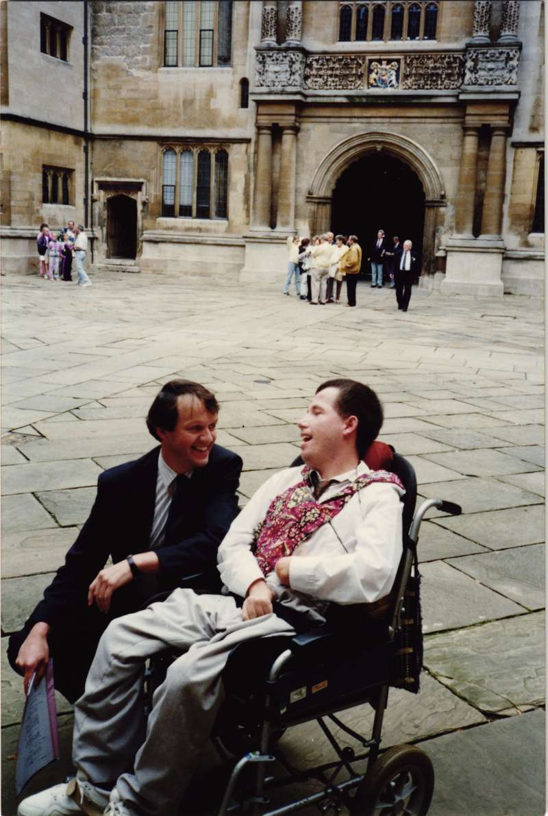 Kevin Whately, actor, crouched down talking to a man in a wheelchair in a courtyard area