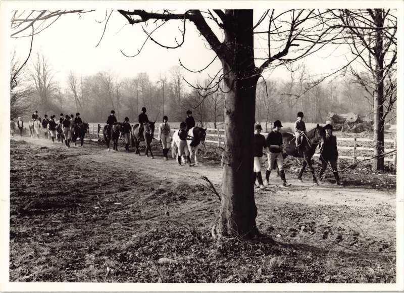 Photo of several people out for a horse ride in the countryside with others leading horses and standing nearby