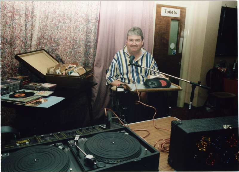 Man in a wheelchair surrounded by vinyl records and record-playing equipment