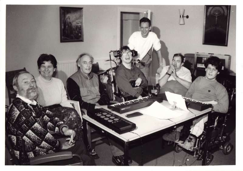 Group of seven people, many in wheelchairs sat around a table with music keyboards