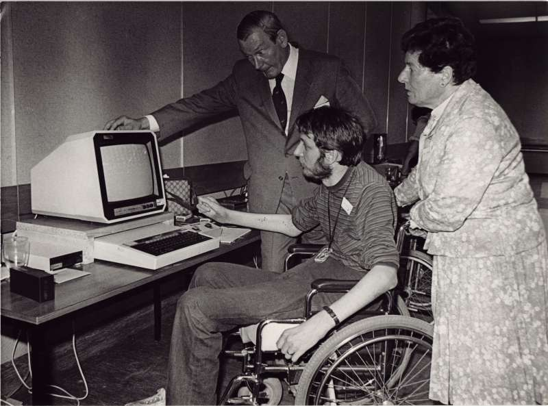 Man in a wheelchair at a computer, with a man and woman watching on