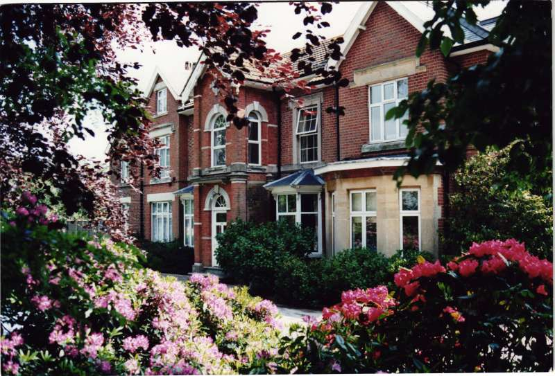 Colour photo of the Heatherley building, taken through trees, with pink and purple flowers in the foreground