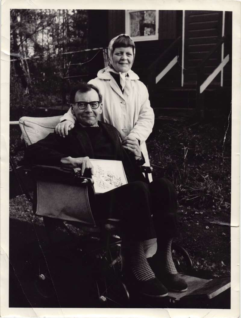 Man in wheelchair holding an anniversary card, with a woman standing beside him in a white coat and headscarf