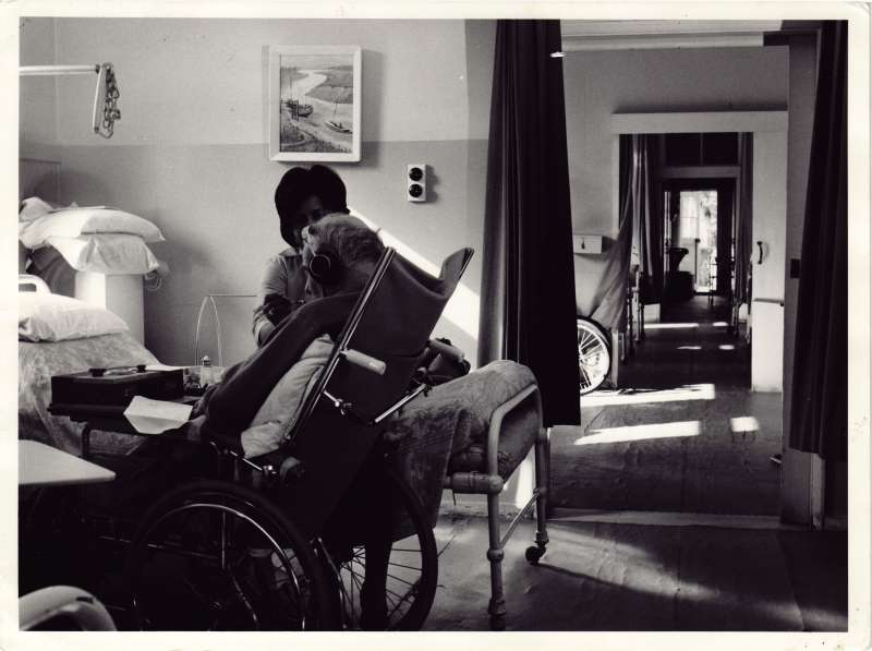 Male resident in a wheelchair wearing headphones being fed by a female carer in his bedroom