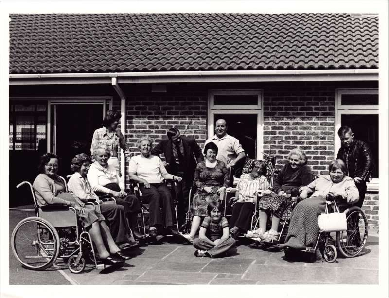 Posed photo of eight female residents in wheelchairs and four members of staff outside a brick building