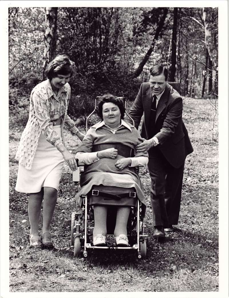 Female resident in a wheelchair being pushed along a woodland path by a man and a woman