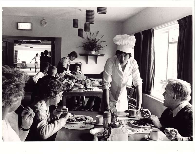 Residents at tables eating a meal and talking to a young man wearing a chef's uniform