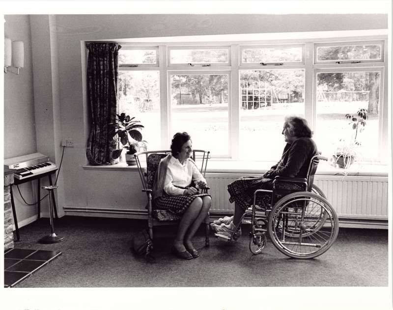 Two women, one in a wheelchair, talking in a lounge in front of a window