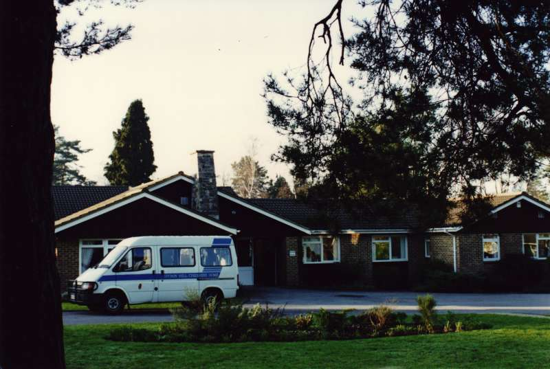 Exterior view of a brick building in gardens with a white ambulance or minibus in the foreground