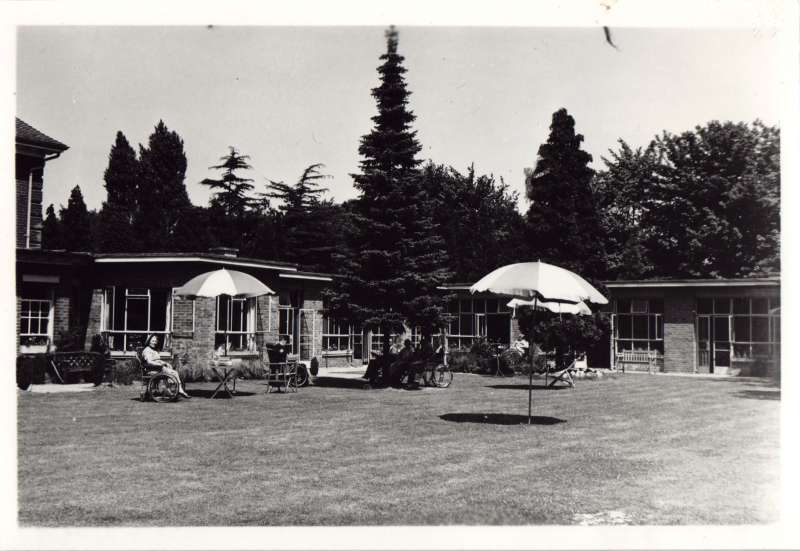 Several people in wheelchairs on a lawn under parasols with a building and trees in the background