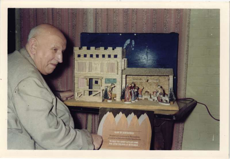 A man in a light grey jacket next to a crib and stable made from from matchsticks