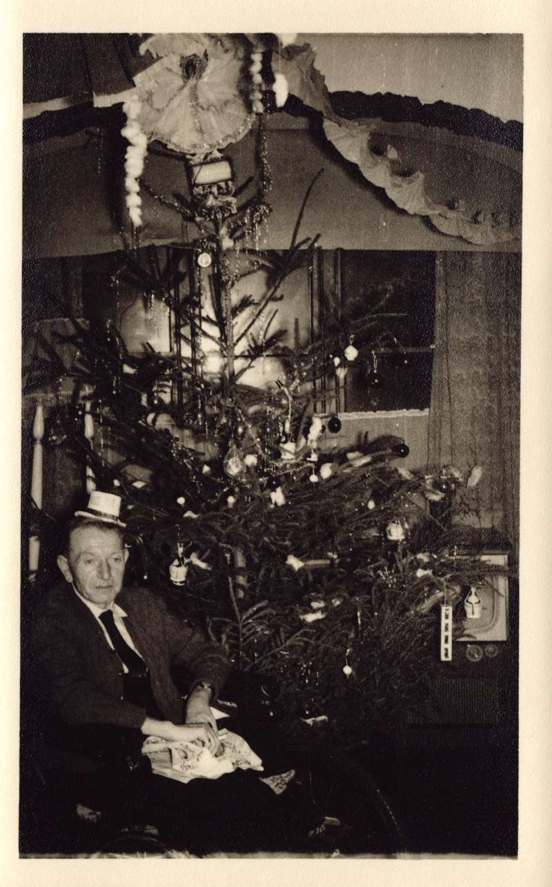 A man in a wheelchair, wearing a mini top hat, sat next to a decorated Christmas tree