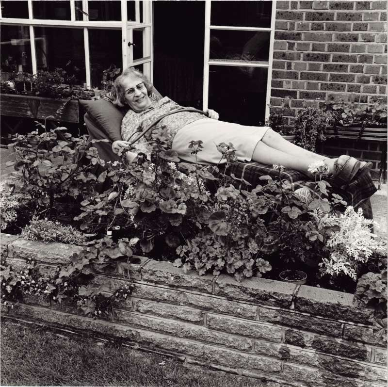 A lady lying on a flat wheelchair holding a hose pipe watering a flower bed