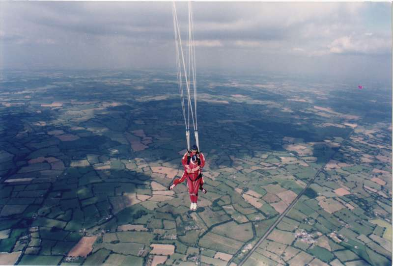 Two men in red parachute jumpsuits and blue hats high above the ground after a parachute jump
