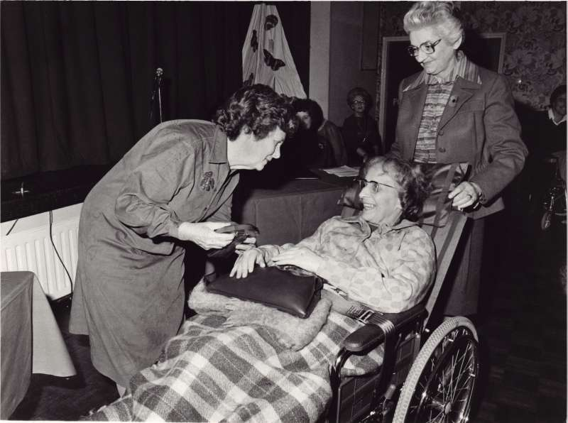 Older lady in a wheelchair with a black handbag on her lap, receiving an award from another lady