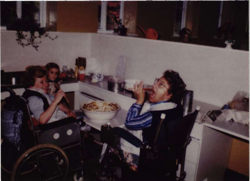 Two women in wheelchairs and a young girl with a cake bowl on a table