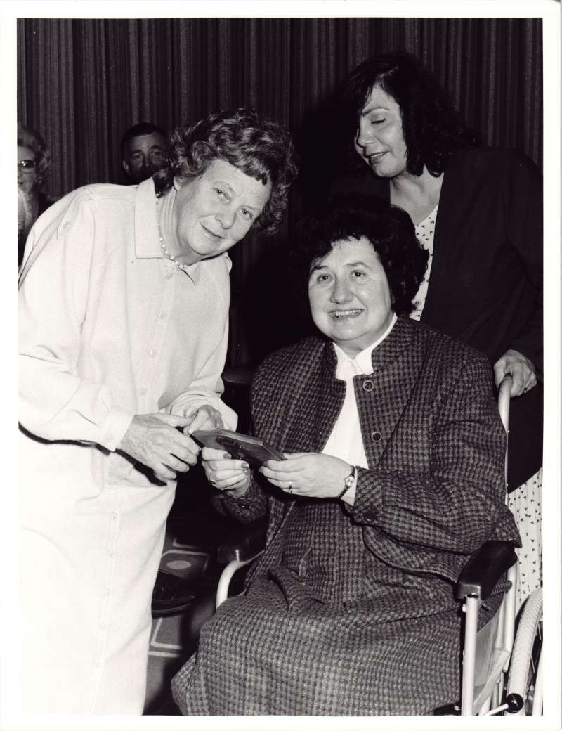 Lady in a wheelchair being presented an award by another lady in a white dress coat