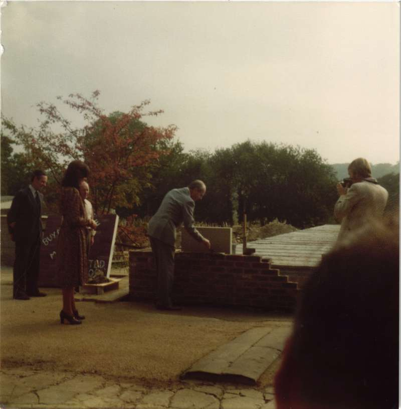 Leonard Cheshire laying mortar for bricks watched by a woman in a dress and photographers