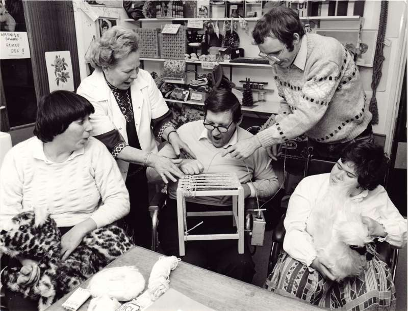 Male resident making a wooden stool with assistance from staff, with two female residents watching on