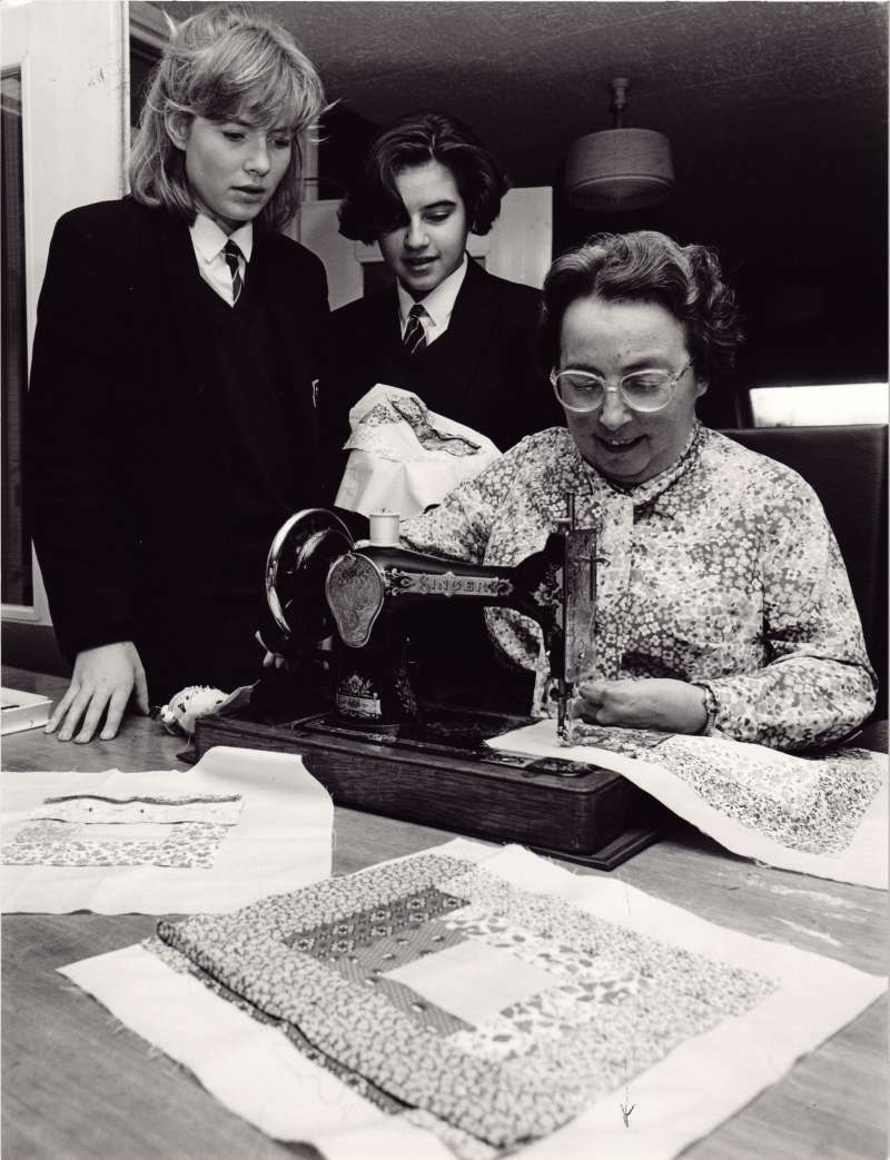 Female resident using a sewing machine, watched on by two schoolgirl volunteers