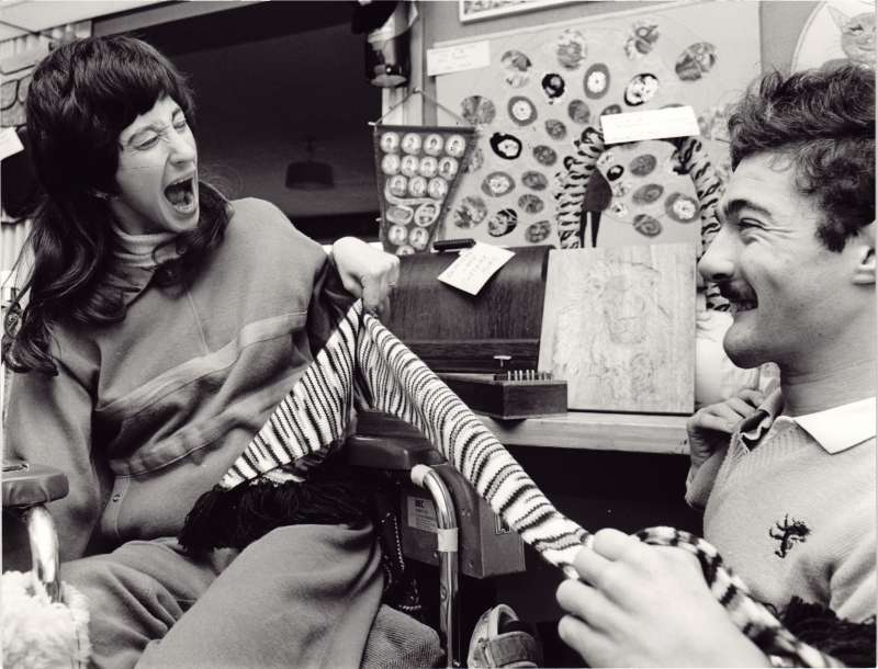 Two residents in wheelchairs holding a black and white striped scarf in the craft room