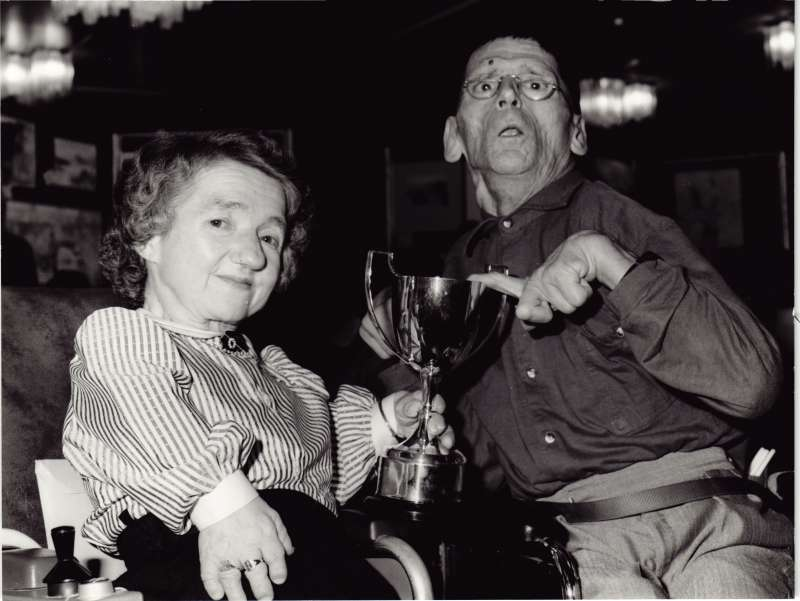 Two people in wheelchairs, a man and a woman, holding a trophy cup