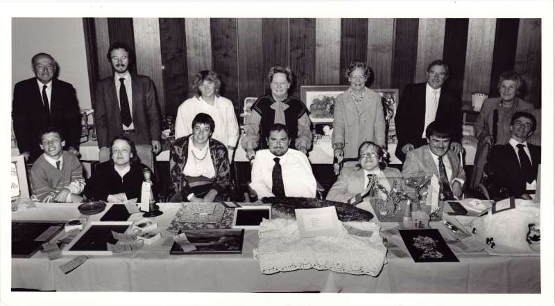 Group photograph of fourteen people sat at a table after receiving an award for their crafts