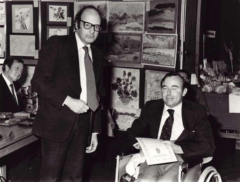 A man in a wheelchair receiving an award certificate for a painting